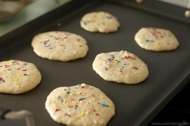 Perfect Birthday Pancakes adding sprinkles