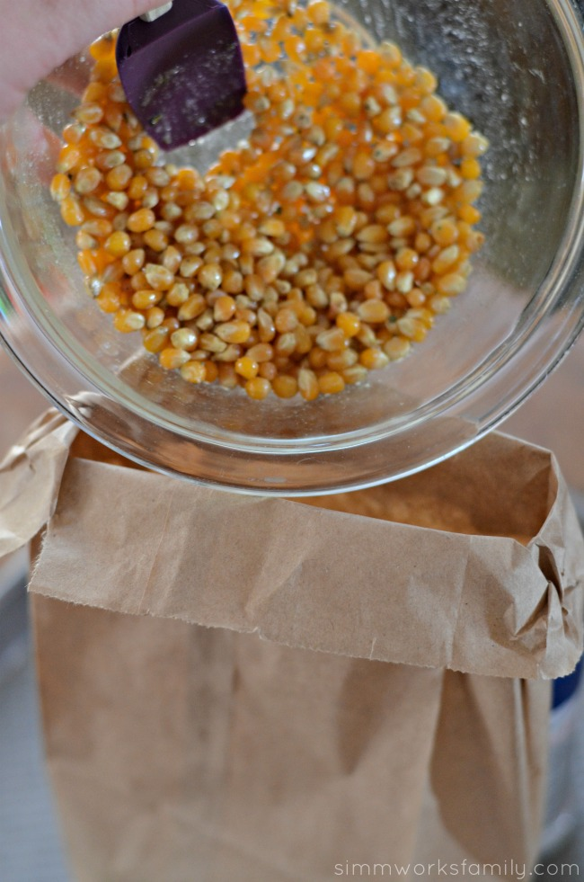 Homemade Microwavable Ranch Popcorn in a Bag pour seasoned kernels in bag